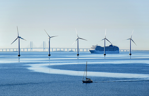 Copenhagen, Denmark - July 15, 2017: A very large passenger ship and a small sailboat pass offshore wind turbines near the Oresund Bridge between Denmark and Sweden.