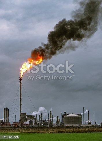 Dark smoke rising at dusk from a large flare flame at Grangemouth Petrochemical Plant in central Scotland.