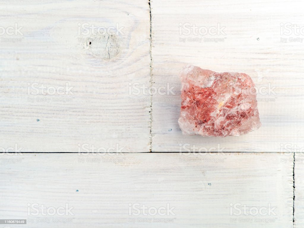 A Large Piece Of Himalayan Pink Salt Rock On A White Wooden