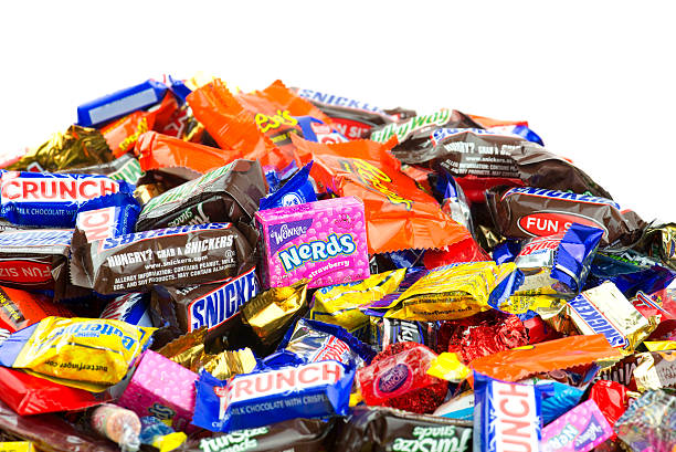 large pile of candy on white background - kit kat stock photos and pictures