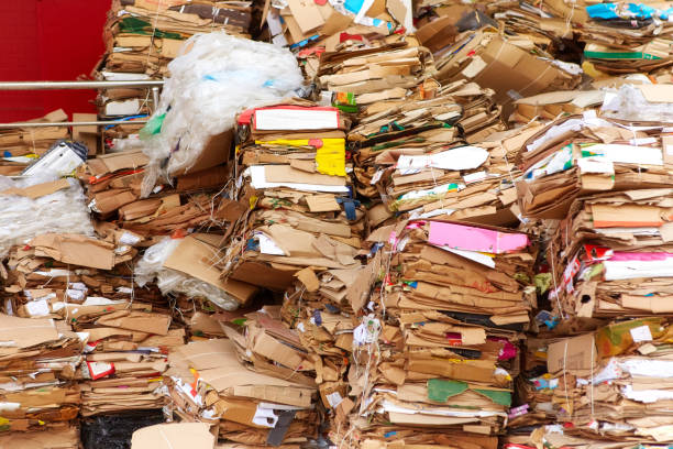 A large pile of cardboard boxes from the goods sold, stored in the back of the supermarket. The concept of urban pollution stock photo