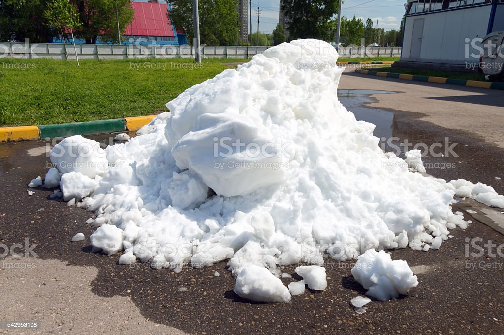 Large pile of dirty snow lying in the puddle stock photo