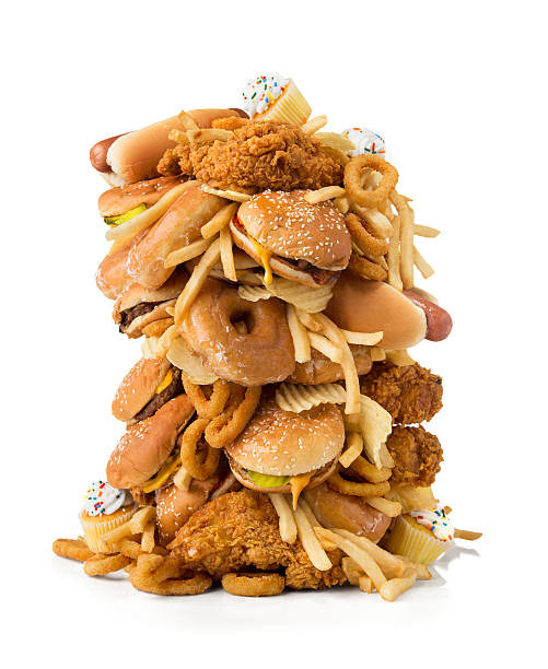 Large pile of junk food A large pile of junk food/fast food consisting of cheeseburgers, hamburgers, hot dogs, french fries, onion rings, cupcakes, potato chips, donuts and fried chicken.  The pile of junk food is isolated on a white background with clipping path.  Please see my portfolio for other food and drink images.  unhealthy eating stock pictures, royalty-free photos & images