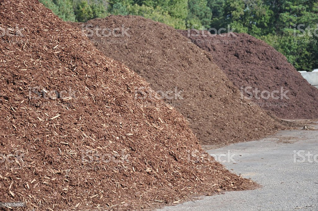 Large piles of mulch on the side of the road stock photo