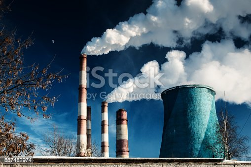 istock large pipes in the industrial zone with voluminous white smoke against the background of a deep blue sky with the moon. 887482974