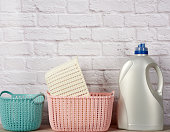 large plastic bottle with liquid detergent and a stack of baskets against a white brick wall background