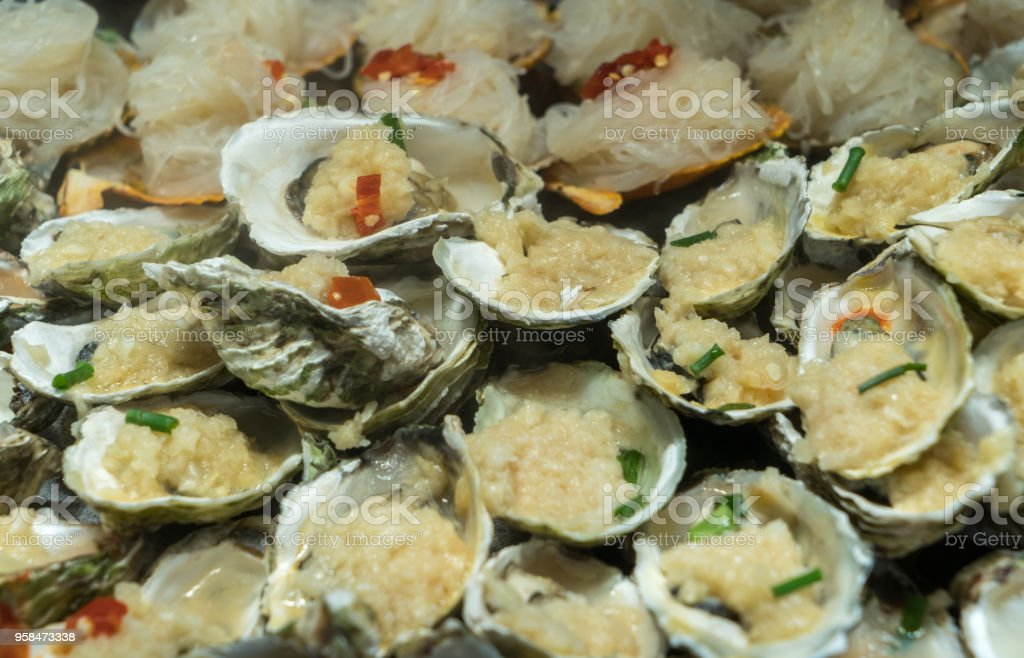 A large plate of roast oysters on the plate stock photo