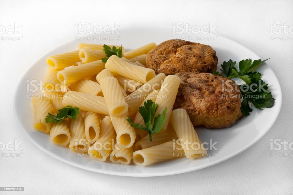 A large plate with pasta and two cutlets, decorated with parsley on a white tablecloth. royalty-free stock photo