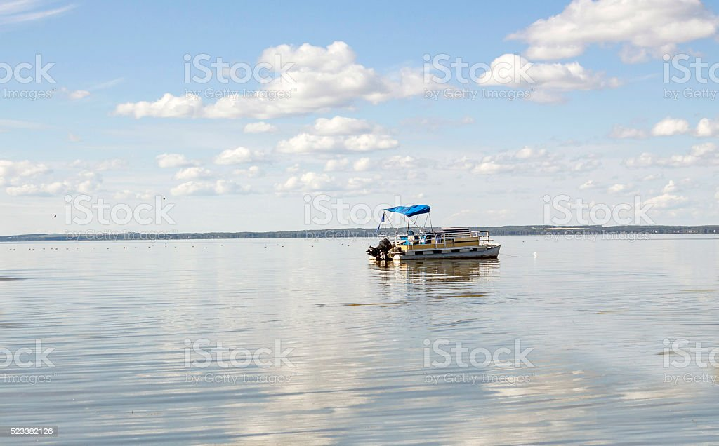 large pontoon boat coasting on a very big lake. stock photo