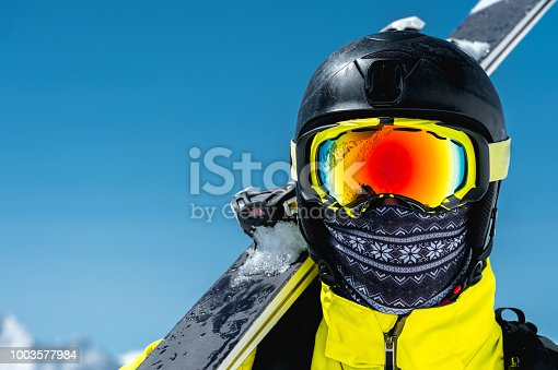 A large portrait of a skier in a protective helmet and glasses - a mask and a scarf next to the skis against the snow-capped mountains of the Caucasus. Skiing,