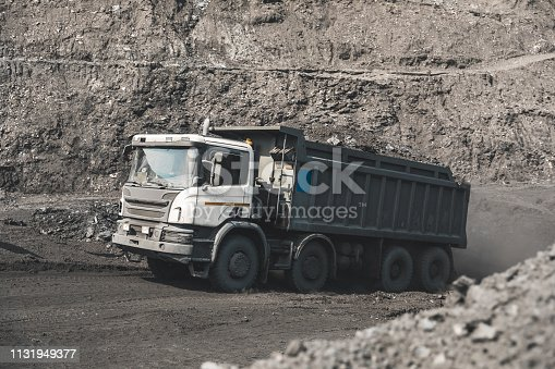 istock Large quarry dump truck. Loading the rock in dumper. Loading coal into body truck. Production useful minerals. Mining truck mining machinery, to transport coal from open-pit as the Coal Production 1131949377
