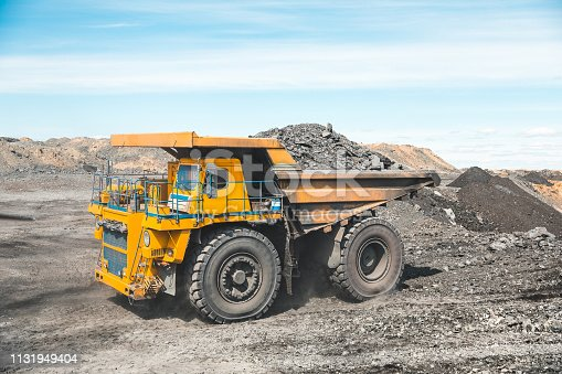 istock Large quarry dump truck. Loading the rock in dumper. Loading coal into body truck. Production useful minerals. Mining truck mining machinery, to transport coal from open-pit as the Coal Production 1131949404
