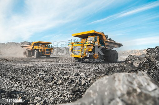 istock Large quarry dump truck. Loading the rock in dumper. Loading coal into body truck. Production useful minerals. Mining truck mining machinery, to transport coal from open-pit as the Coal Production 1131949965