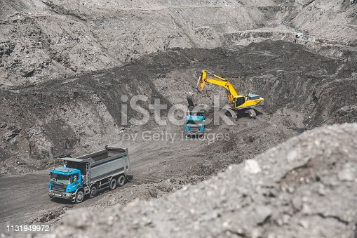 istock Large quarry dump truck. Loading the rock in dumper. Loading coal into body truck. Production useful minerals. Mining truck mining machinery, to transport coal from open-pit as the Coal Production 1131949972