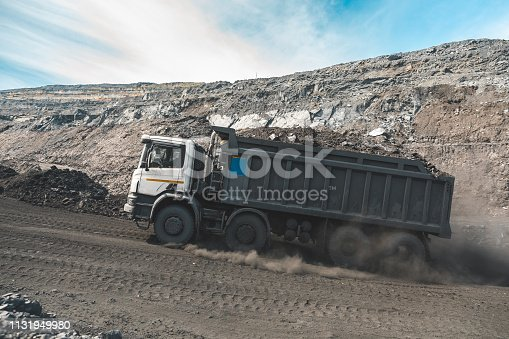 istock Large quarry dump truck. Loading the rock in dumper. Loading coal into body truck. Production useful minerals. Mining truck mining machinery, to transport coal from open-pit as the Coal Production 1131949980