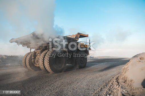 istock Large quarry dump truck. Loading the rock in dumper. Loading coal into body truck. Production useful minerals. Mining truck mining machinery, to transport coal from open-pit as the Coal Production 1131950002