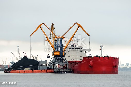 istock Large red cargo ship loading 665493732
