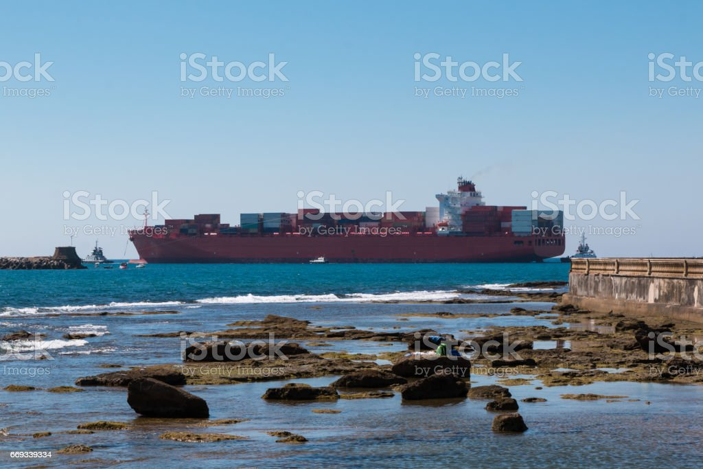 Large Red Container Ship Near Coastline stock photo