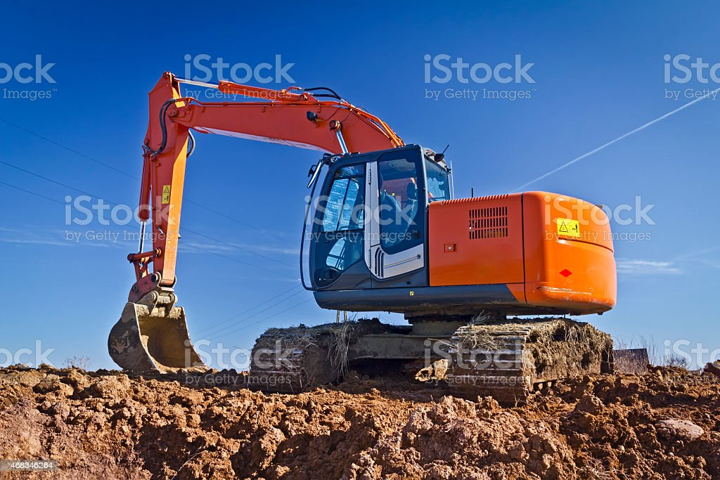 Large red excavator in road construction stock photo