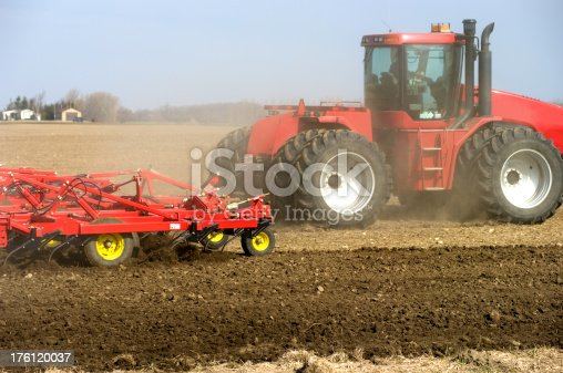 A large articulating tractor cultivating a farm field in preparation for spring seeding. (note - some dust in the air)Similar images.