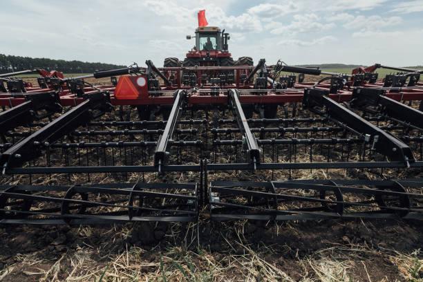 großer roter Traktoranhänger für Bodenbearbeitung bei der Aussaat im Frühjahr in Russland – Foto