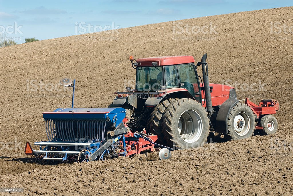 Large red tractor working in the field. stock photo