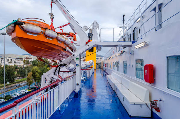A large rescue boat is attached to the brackets on the deck of the ship. stock photo