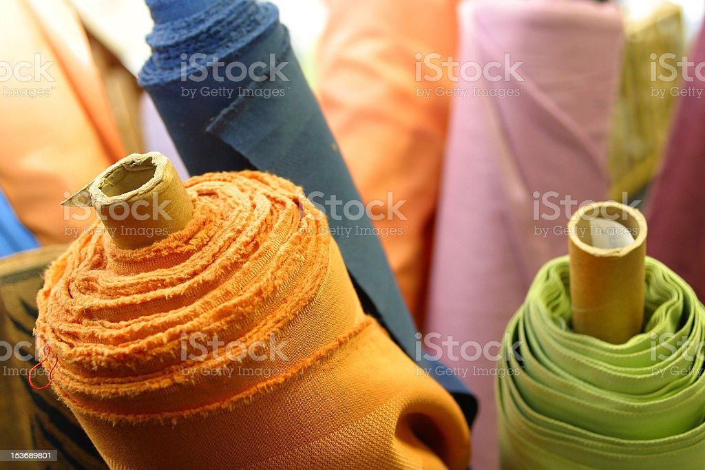 Large rolls of orange green and blue material stock photo