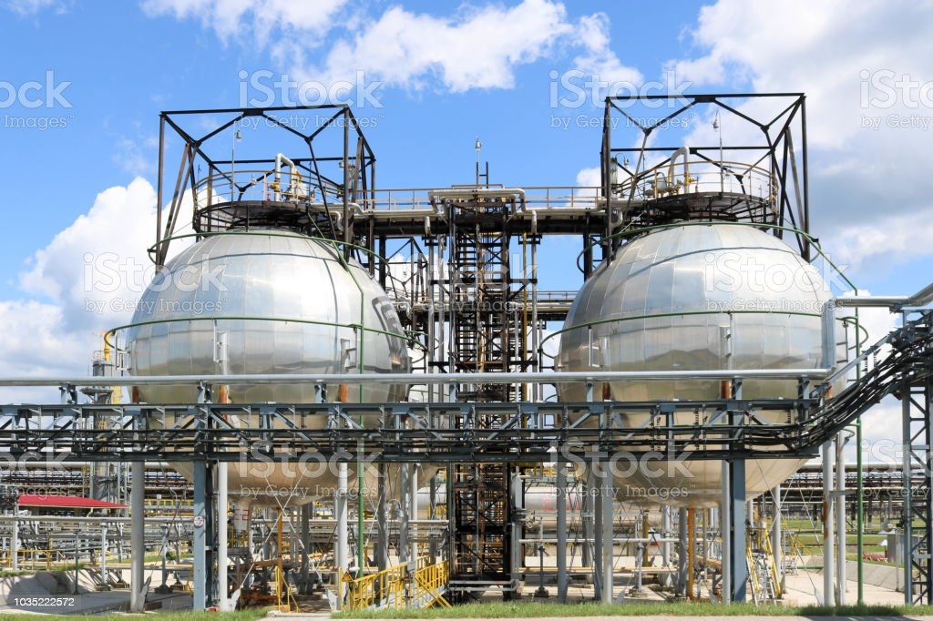 A large round ball-shaped shiny metallic high-pressure iron storage tank for ammonia is strong with pipes and equipment at the petrochemical chemical refinery industrial refinery stock photo