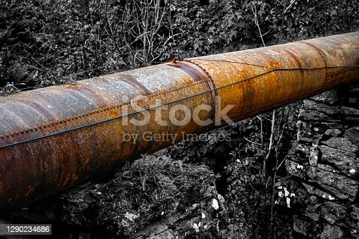 Large rusted and old industrial pipeline running through rough nature.