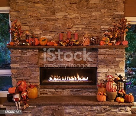 istock Large, Rustic Stone Fireplace All Glowing with Soothing Flames with Pumpkins and Autumn Holiday Decor 1180062357