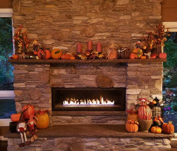 Large, Rustic Stone Fireplace All Glowing with Soothing Flames with Pumpkins and Autumn Holiday Decor stock photo