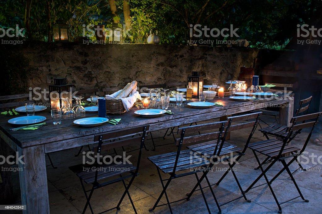Mesa grande rústica preparada para um jantar ao ar livre à noite - foto de acervo