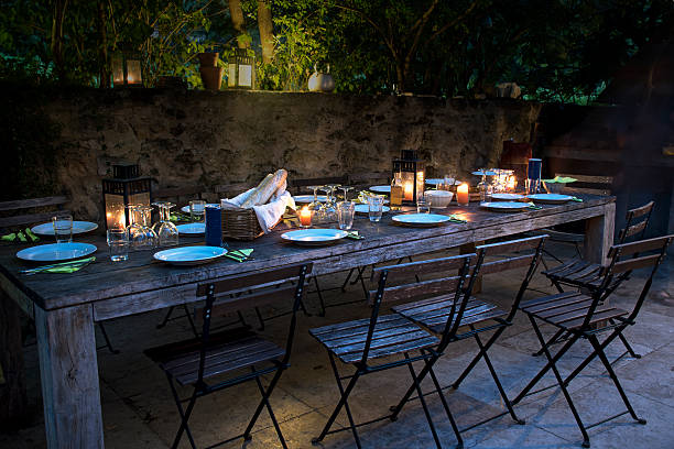 large rustic table prepared for a outside dinner at night stock photo