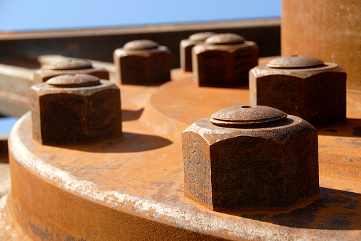 Several rusty bolts attached to a very large piece of machinery.