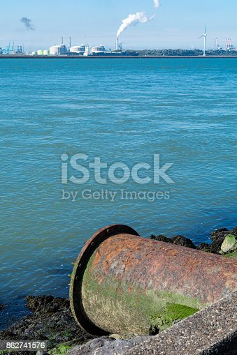 Large rusty end of pipeline with rotterdam harbor europe liquid gas strorage and coal power plant in backdrop at the harbor exit end of the rhine