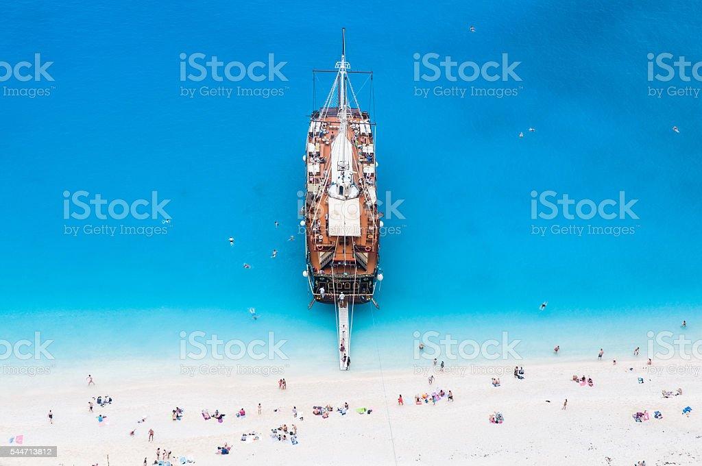 large sail cruise ship anchored at white sand beach stock photo