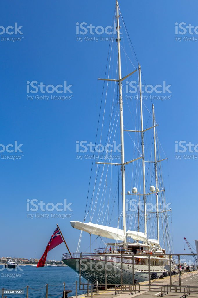 A large sailing ship stands in the port on the dock with the sails lowered. stock photo