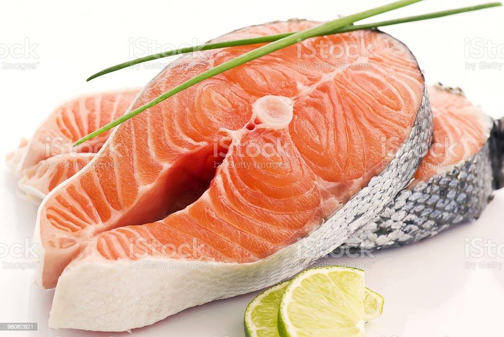 Large salmon steaks with lemon garnish royalty-free stock photo