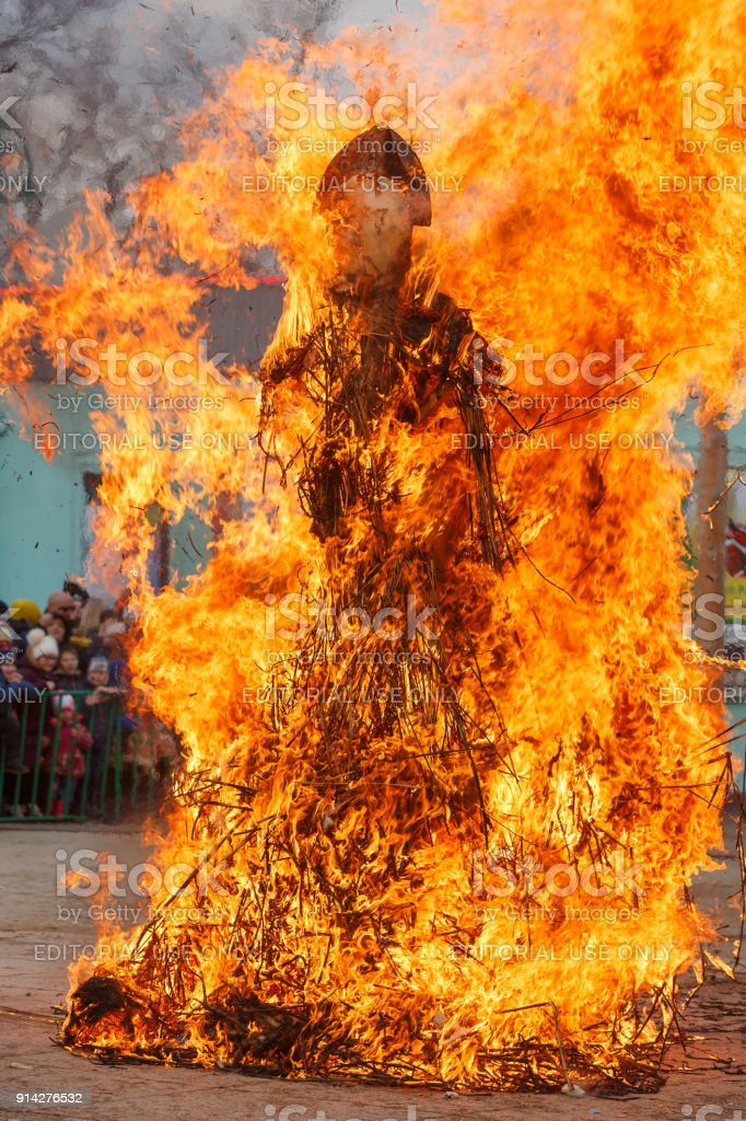 large scarecrow of maslenitsa burns on the stage of the city park