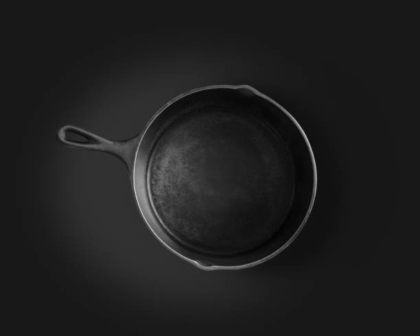 Large seasoned cast iron skillet with a black background stock photo