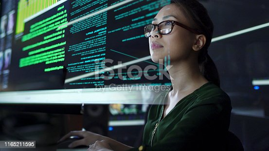 Stock photo of a young Asian woman looking at see through data whilst seated in a dark office
