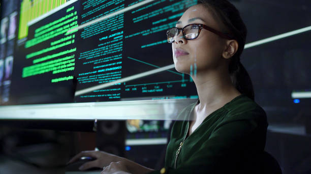 Large see through screen Stock photo of a young Asian woman looking at see through data whilst seated in a dark office data stock pictures, royalty-free photos & images