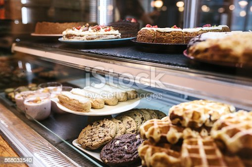 istock Large selection of cakes and pastries on the counter in a cafe. Sale of delicious sweets. 868033540