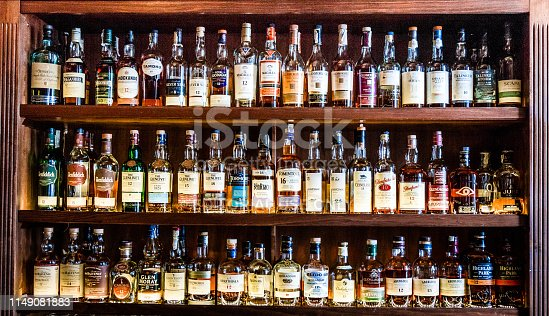 London, UK - 10 May, 2019: Color image depicting a huge selection of different malt Scotch whisky bottles in a row and displayed on wooden shelves at a bar in London, UK. The whisky is mainly Scottish single malt and comes from a range of different distilleries. Room for copy space.