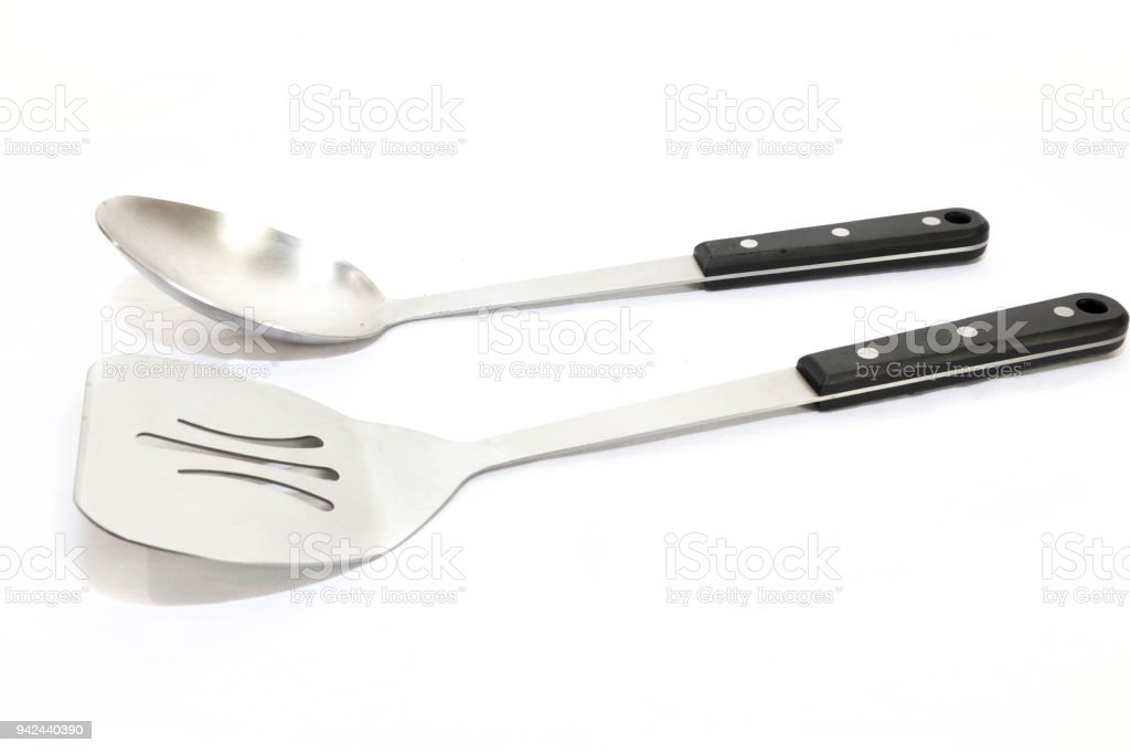 Large serving spoon and a spatula with black handles on a white bacground stock photo