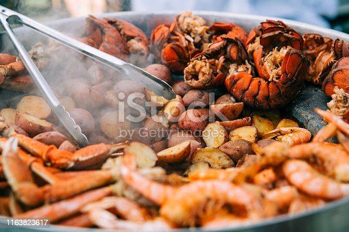 Large sheet of grilled seafood at a county fair festival. This includes lobsters, shrimp and crab