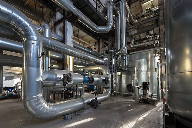 large silver pipes and tanks inside an electric power plant - cogeneration plant stock photos and pictures