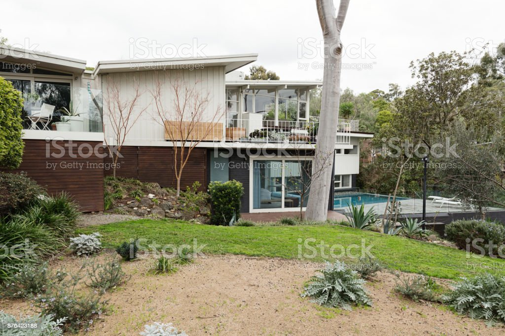 Large sixties style Australian home exterior set in beautiful landscaped gardens stock photo