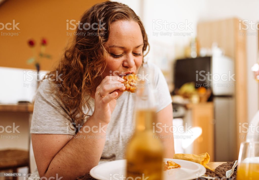 large size woman eat pizza at home